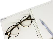 Ojos y pluma negros de vidrios en el cuaderno blanco Foto de archivo libre de regalías