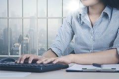 Okänd affärskvinna som arbetar vid fönstret arkivfoton
