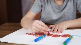 Okänd barnteckning med ljusa kulöra blyertspennor på vitbok, medan sitta på tabellen Begreppet av utveckling lager videofilmer