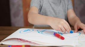 Okända barnattraktioner med ljusa blyertspennor, medan sitta på tabellen Utveckling och utbildning av barn av förträningen arkivfilmer