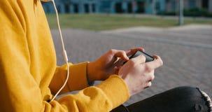 Okända manliga händer i gul tröja är spela, smsa och bläddra på mobiltelefonen längd i fot räknat 4k Ingen framsida stock video