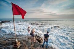 Okända turister som står på att krascha vågor Royaltyfri Bild