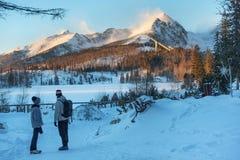 Okänt folk som står nära Strbske Pleso sjön och långt ser till de snöig bergmaxima av den höga Tatrasen Royaltyfri Fotografi