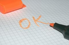 OK. Word OK written on white paper with grid by orange pen Stock Image