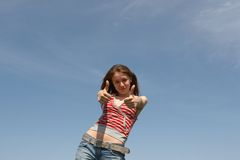 OK. Prety young girl on a background of the blue sky Royalty Free Stock Image