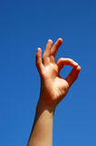 Ok. Womans hand on sky background Royalty Free Stock Photography