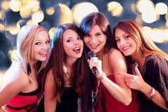 唱卡拉OK演唱的四个美丽的女孩 免版税库存图片