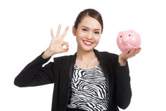 与猪硬币银行的亚洲女商人展示OK 免版税库存图片