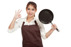 OK asiatique d'exposition de cuisinière de fille avec la poêle Images stock