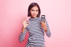 OK asiatique d'exposition de femme avec la calculatrice photos libres de droits