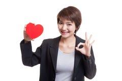 OK asiatique d'exposition de femme d'affaires avec le coeur rouge Photo stock
