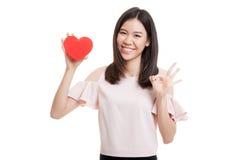 OK asiatique d'exposition de femme d'affaires avec le coeur rouge Images stock