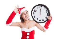 OK asiatique d'exposition de fille de Santa Claus de Noël avec l'horloge à minuit Image libre de droits