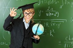 Ok education. Portrait of a schoolboy in big round spectacles and academic hat at a classroom Stock Images