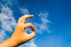 OK hand sign. On the blue sky background stock image