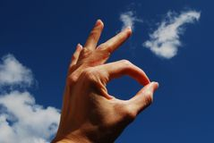 OK Hand Singal Left. OK hand singal with left hand. background of clouds and blue sky Royalty Free Stock Image