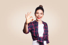 OK. Happy toothy smiley young woman showing OK sign with fingers. Studio shot on beige background. focus on hand Stock Photos