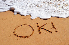 Ok written in sand. Ok! message written in the sand with a wave approaching stock photo