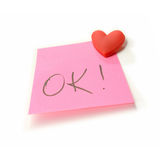 OK Post Note. Studio macro of post note with handwritten OK pinned to a white background with a red heart shaped pin. Copy space Stock Photo