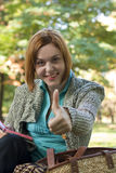 OK sign. Young red-haired woman reading in the park and showing OK sign Stock Photos