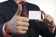 Ok sign. Elegnant business man showing ok gesture with white card in his hand out of focus on white background Royalty Free Stock Photography