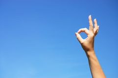 Ok sign hand against blue sky Stock Photo