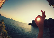 Ok sign making of hands. Against bright sea sunset Royalty Free Stock Photography