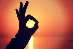 Ok sign making of hands. Against bright sea sunset and sunny golden way at water Stock Images
