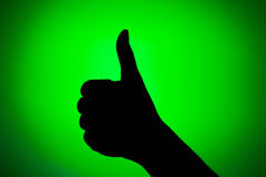 OK sign. Silhouette of hand with thumb up on a green background Royalty Free Stock Photography