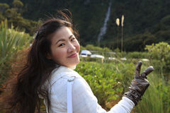 OK. Smiling asian girl in travel location Royalty Free Stock Image