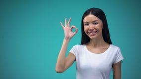 Ok tecken för gladlynt asiatisk kvinnavisning som isoleras på blå bakgrund, mall stock video