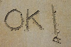 Ok word spell written on beach wet sand Stock Images
