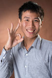 Ok. Young Chinese frank businessman give you an Okay gesture, closeup portrait in studio royalty free stock photo