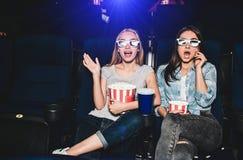 Okaleczać i excited dziewczyny siedzą w kinowej sala i oglądają film Zadziwiają Także kosze dziewczyny Obrazy Stock