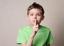 Okaleczająca chłopiec robi cisza gestowi Dzieciaka kładzenia palec do wargi zdjęcie stock
