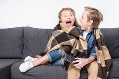 Okaleczający dzieciaki w powszechnym obsiadaniu na kanapie i patrzeć each inny obraz stock