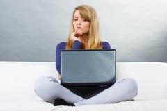 Okaleczający kobiety obsiadanie na kanapie i patrzeć laptop, nowożytna technologia Obrazy Stock