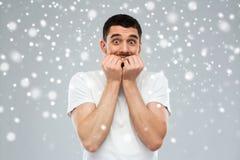 Okaleczający mężczyzna w białej koszulce nad śnieżnym tłem zdjęcia royalty free