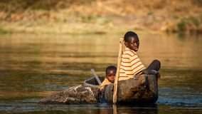 Okavango Brothers. Two brothers fishing on a small boat at okavango river in the evening sun royalty free stock image