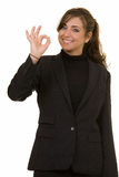 Okay. Attractive brunette woman in professional business suit standing on white smiling making the okay sign with her hand Royalty Free Stock Images