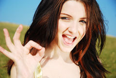 Okay!. A beautiful young woman giving you the okay sign in a field with a blue sky royalty free stock photography