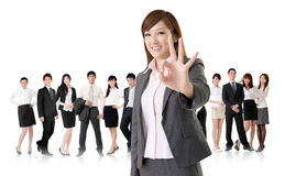 Okay gesture. Smiling business executive women of Asian give you an okay sign in front of her team isolated on white background Royalty Free Stock Photo