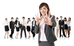 Okay gesture. Smiling business executive women of Asian give you an okay sign in front of her team isolated on white background Stock Photography