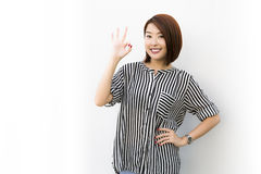 Okay lady. A charming Asian lady signal okay sign on white background Royalty Free Stock Images