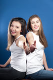 Okay by Two happy young beautiful woman friends. Two happy young beautiful women friends smiling with thumbs up on blue background Stock Photo