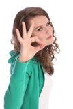 Okayhandzeichenerfolg durch lächelndes Jugendlichmädchen Stockfotografie