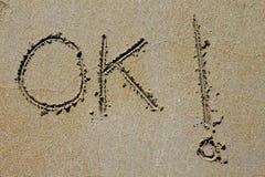 Okaywortbann geschrieben auf nassen Sand des Strandes Stockbilder