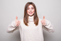 Okey sign girl in sweater in studio. Isolated gray background Stock Images