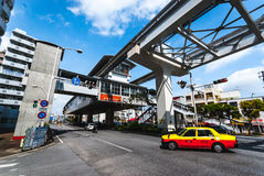 Okinawa Monorail. Okinawa, Japan - March 30. 2015: Taxi passes under the `Yui Rail` or Okinawa Urban Monorail tracks at `Asato` station.  The signs on the left Royalty Free Stock Photo