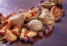 Okkernoot, gedroogd fruit en droge rozebottels op een houten raad Royalty-vrije Stock Foto's